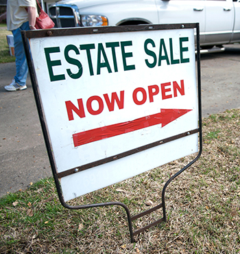 yard sign in lawn advertises an estate sale